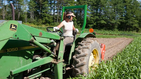 woman on tractor plowing field