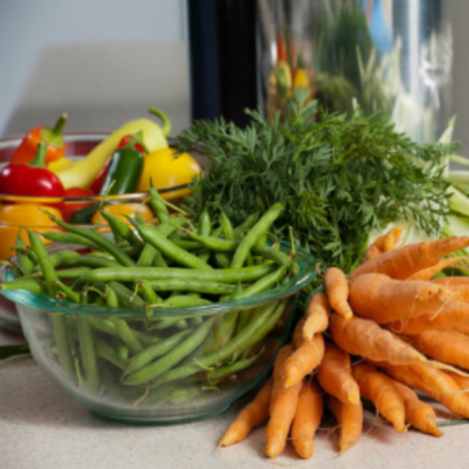 photo of glass of color peppers, glass of green beans and a bunch of carrots on kitchen counter