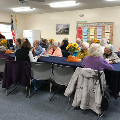 group photo of homemaker volunteers sitting around tables at their fall meeting watching a presentation