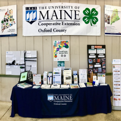 Oxford County Cooperative Extension booth at Fryeburg fair with banner and flyers