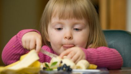 Young girl eating fruit
