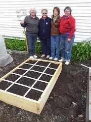 Gardeners standing next to a raised bed garden