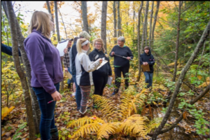 4-H volunteers and youth in the woods