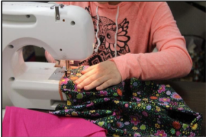 child sewing on a sewing machine