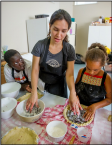 Adult teaching 2 youth how to bake