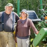farm couple in front of tractor