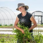 woman farmer in front of hoop house