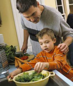 father and son wash vegetables for a salad
