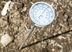 thermometer in compost reads 140 degrees F; photo by Edwin Remsberg, USDA