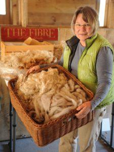 sheep producer holding a basketful of wool; photo by Edwin Remsberg, USDA