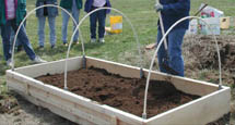 Master Gardeners filling a raised bed garden