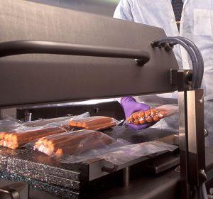microbiologist Glenn Boyd vacuum-seals hotdogs to get them ready for irradiation