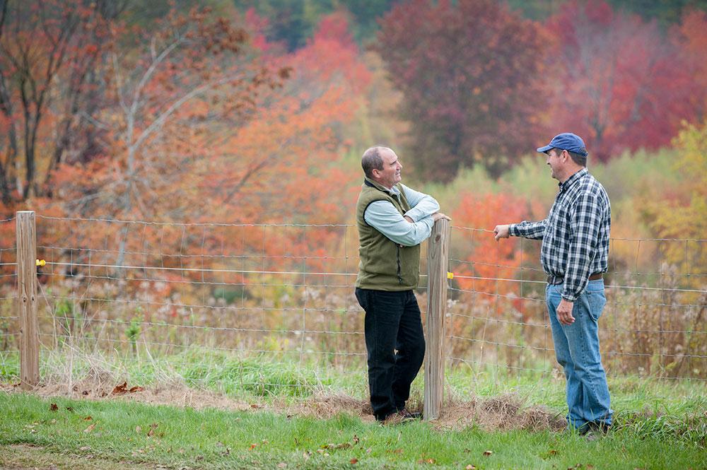 Extension educator talks with a farmer
