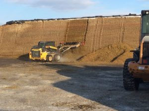 "Facer in action ""raking"" the face of a bunker of corn silage."
