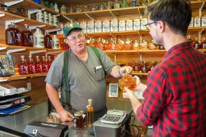 Maple syrup producer selling added value products to a customer in his shop