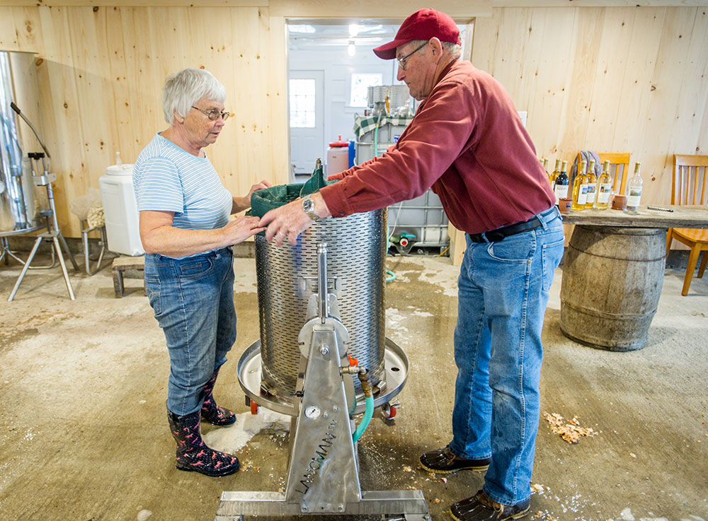 Two older farmers pressing apple cider
