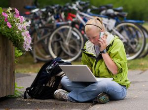 teen sitting cross-legged on ground with open laptop and talking into a cellphone