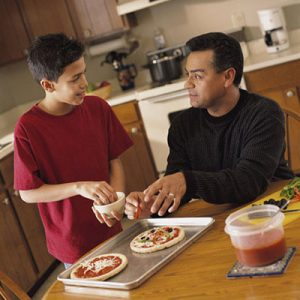 Father and teenage son making pizzas