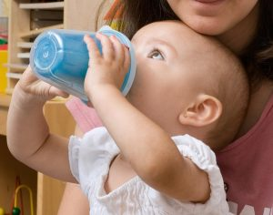 Baby sits in mother's lap and drinks from a child's cup