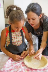 Mom and daughter making a pie crust