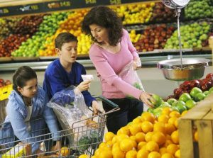 mom, son, and daughter shop for produce in the grocery store