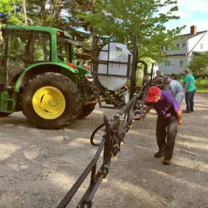 farmer checking the sprayer attachment on his tractor