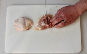 Photo of raw chicken showing removal of the bone from the thigh.