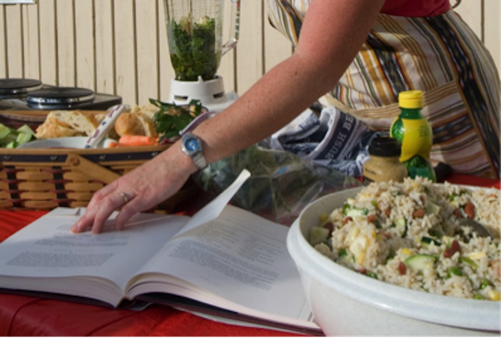 woman with salads and recipe book