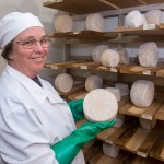 goat cheese producer with wheels of hard cheese