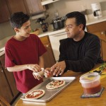 dad and teen making pizza