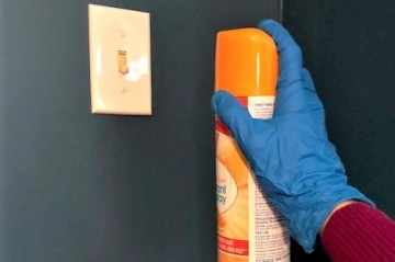 An aerosol disinfectant posed to spray a light switch