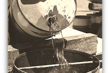 A drum of insecticide being poured into a second bin