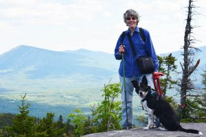 Sally and her dog Reece pause on an overlook while hiking in the Bigelow Preserve