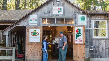 UMaine Extension educator Kathy Hopkins talks with a maple syrup producer in his sugar shack