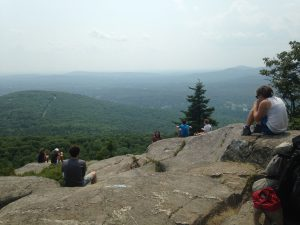 campers rest and take in the view from the top of a mountain