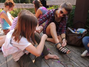 camp staff shows campers how to make bracelets