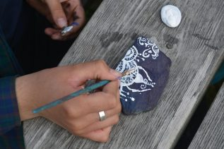 girl painting rock