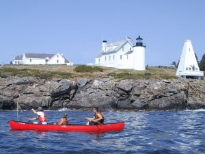 3 teens paddle canoe across the bay in front of lighthouse