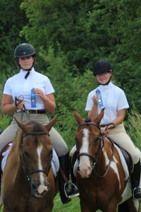 Two 4-H members and horses with first place ribbons in English Equitation at the Bangor Fair