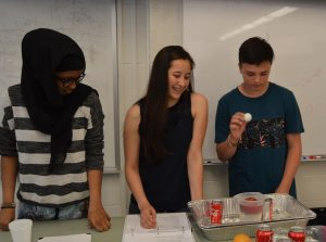 Teen leaders lead a science experiment.