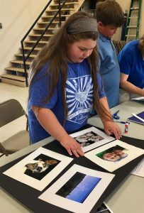 A 4-H member works on mounting her photos for the Washington County 4-H Photo Contest.