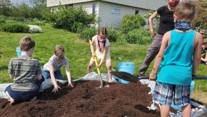 Youth participate in a gardening activity during June Jamboree.