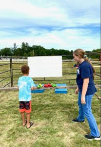 4-H member helps youth play a game.