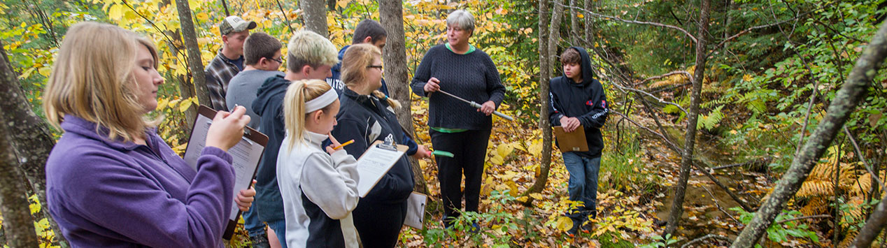 Youth take notes during an outdoor classroom activity at Bryant Pond