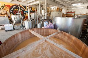 Food safety expert with brewery business owner in with fermentation vats