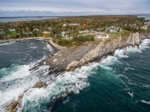 aerial view of light house on rocky Maine coast
