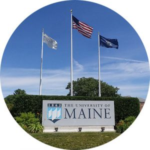 The University of Maine entrance sign with 3 flags (US, Maine, and UMaine)
