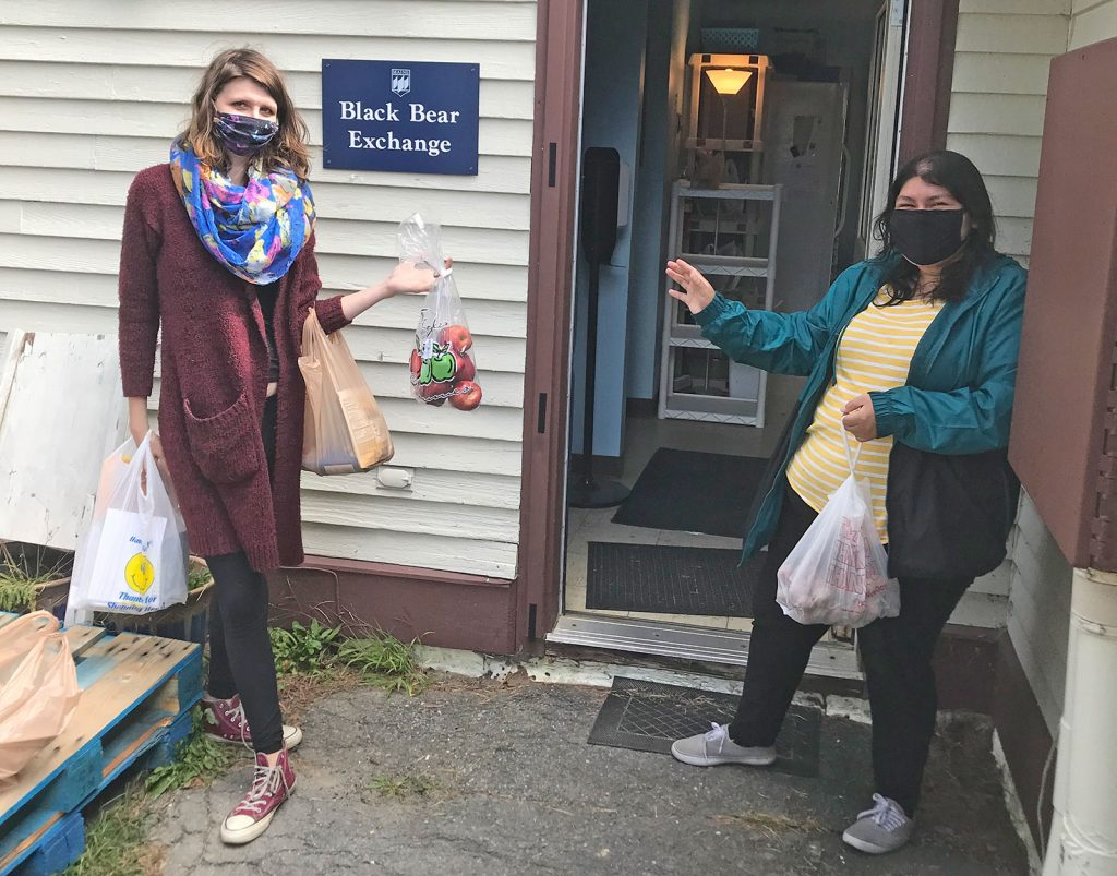 two masked students outside the Black Bear Exchange with food bags