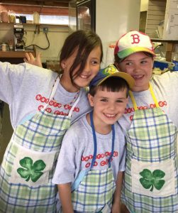 3 4-Hers wearing matching cooking aprons with the 4-H logo