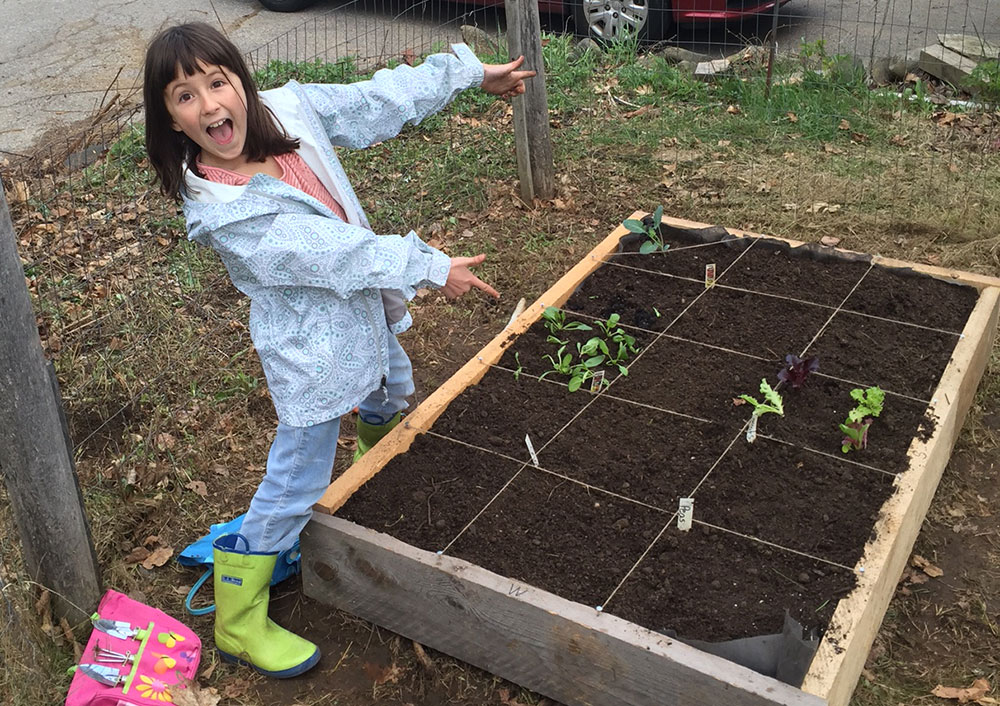 """Kids Can Grow"" youth participant stands proudly next to her newly planted square-foot, raised-bed garden"